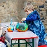 Pintura do rapaz pequeno e da menina com cores na abóbora Imagem de Stock Royalty Free