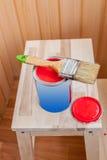 Pintura e escova vermelhas na cadeira de madeira Imagens de Stock