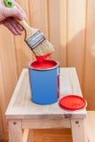 Pintura e escova vermelhas na cadeira de madeira Fotos de Stock
