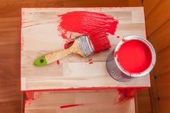 Pintura e escova vermelhas na cadeira de madeira Foto de Stock