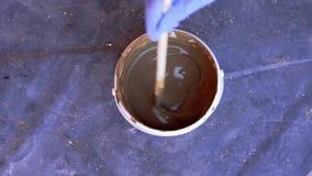 Pintura e reparos - a pintura na cubeta é agitada com uma vara, movimento lento video estoque