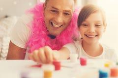 Pintura encantada feliz del hombre así como su hija Fotos de archivo