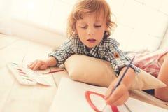 Pintura encantada positiva del niño Foto de archivo