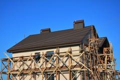 Pintura, estuque e emplastro da parede exterior da fachada do andaime da casa com telhar novo do metal exterior Foto de Stock