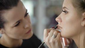 Pintura experimentada del artista de maquillaje muy rápidamente los labios de la muchacha con la ayuda del lápiz cosmético de alt almacen de metraje de vídeo