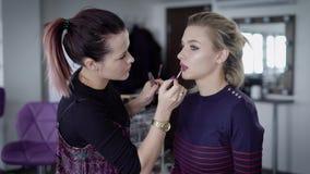Pintura experimentada del artista de maquillaje muy rápidamente los labios de la muchacha con la ayuda del lápiz cosmético de alt metrajes