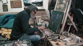 A pintura farpada, grisalho do homem na lona 4K filme