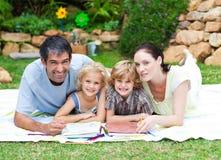 Pintura feliz da família em um parque que sorri na came Fotografia de Stock Royalty Free