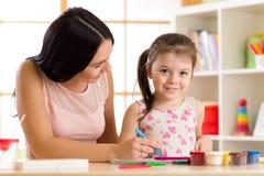 Pintura feliz da filha da mãe e da criança com lápis fotos de stock royalty free