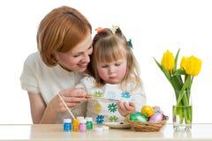 Pintura feliz da filha da mãe e da criança em ovos da páscoa imagem de stock