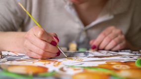 Pintura femenina de las manos del primer con el pequeño cepillo en lona numerada metrajes