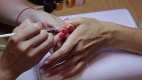 Pintura femenina del clavo Amo de la manicura que crea una pendiente con un cepillo en clavo del pulgar del cliente Opinión del p almacen de video