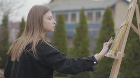 Pintura joven bonita de la muchacha que fuma en lona mientras que se sienta en el patio trasero al aire libre Artista acertado ap almacen de metraje de vídeo
