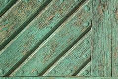A pintura lascada na porta das placas idosas texture o fundo foto de stock