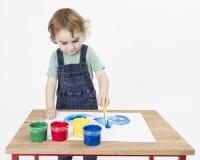 Pintura linda de la muchacha en el pequeño escritorio imagen de archivo libre de regalías