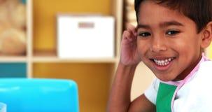 Pintura linda del niño pequeño en la tabla en sala de clase metrajes