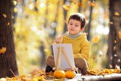 Pintura linda del niño pequeño en parque de oro del otoño Fotos de archivo