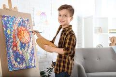 Pintura linda del pequeño niño en el caballete fotografía de archivo