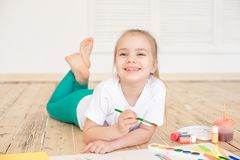 Pintura loura pequena da menina no Livro Branco grande ao colocar no assoalho dentro imagem de stock