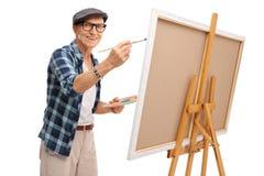 Pintura madura alegre del artista en una lona Imagenes de archivo