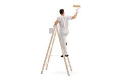 Pintura masculina del decorador con un rodillo imagenes de archivo