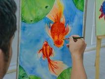 Pintura masculina joven de los pescados de la acuarela del dibujo del artista fotografía de archivo