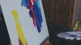 Pintura moderna Lanzamiento del primer de la mano femenina, que hace manchas amarillas grandes con una espátula en la lona E libre illustration