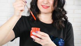 Pintura nas aquarelas Artista fêmea que põe a escova de pintura no frasco de vidro com água Retrato do pintor f?mea video estoque