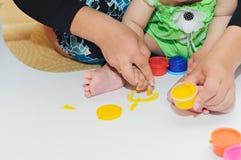 Pintura pequena do bebê por suas mãos em uma casa com mãe Fotos de Stock