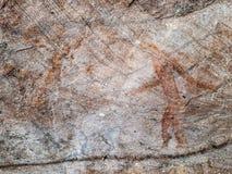 Pintura pré-histórica dos homens nas ações na rocha pintada com cor vermelha pelo ser humano que vivem na área sobre mil anos há fotografia de stock