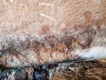 Pintura pré-histórica dos homens nas ações na rocha pintada com cor vermelha pelo ser humano que vivem na área sobre mil anos há imagem de stock