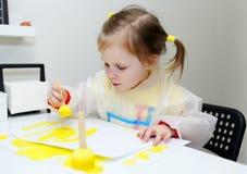 Pintura preciosa linda de la niña con el cepillo de la espuma en casa fotos de archivo libres de regalías