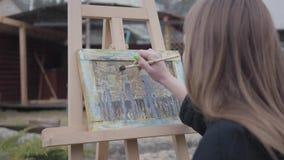 Pintura profesional de la chica joven en lona mientras que se sienta en el patio trasero al aire libre Artista acertado apasionad almacen de metraje de vídeo