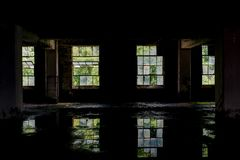 Pintura que refleja en aguas inmóviles - fábrica de cristal abandonada de Windows y de la peladura Imagen de archivo