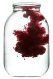 Pintura roja que remolina en agua Imagenes de archivo