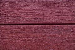 Pintura roja vieja agrietada en una superficie de madera Imagenes de archivo