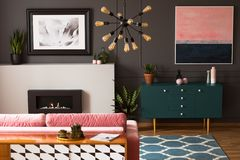 Pintura rosada sobre el gabinete verde en interior plano gris con la chimenea delante del sofá fotografía de archivo