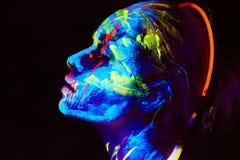 A pintura UV da arte corporal de helloween o guerreiro africano fêmea