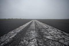 A pintura velha na pista de decolagem no dia nebuloso Imagem de Stock Royalty Free