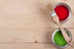 Pintura verde e vermelha no banco com a escova no fundo de madeira claro com espaço da cópia para seu texto Vista superior imagem de stock royalty free