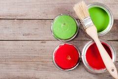 Pintura verde e vermelha no banco com a escova no fundo de madeira velho com espaço da cópia para seu texto Vista superior foto de stock