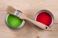 Pintura verde e vermelha no banco a reparar e escovar no fundo de madeira claro imagens de stock royalty free