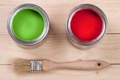 Pintura verde e vermelha no banco a reparar e escovar no fundo de madeira claro fotografia de stock