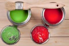 Pintura verde e vermelha no banco a reparar e escovar no fundo de madeira claro fotos de stock royalty free