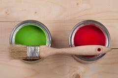 Pintura verde e vermelha no banco a reparar e escovar no fundo de madeira claro imagem de stock