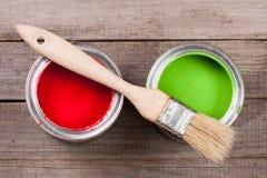 Pintura verde e vermelha no banco a reparar e escovar no fundo de madeira velho fotografia de stock
