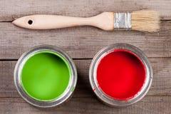 Pintura verde e vermelha no banco a reparar e escovar no fundo de madeira velho foto de stock royalty free