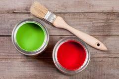 Pintura verde e vermelha no banco a reparar e escovar no fundo de madeira velho imagens de stock royalty free
