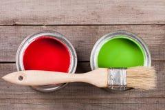 Pintura verde e vermelha no banco a reparar e escovar no fundo de madeira velho foto de stock