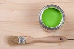 Pintura verde no banco a reparar e escovar no fundo de madeira claro com espaço da cópia para seu texto Vista superior imagem de stock